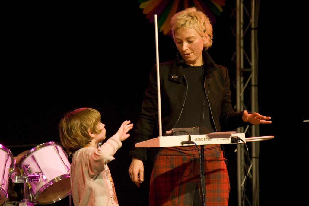 Theremin player Barbara Bucholz teaching how to play the theremin to a young kid. The theremin is tVOX tour made by George Pavlov.